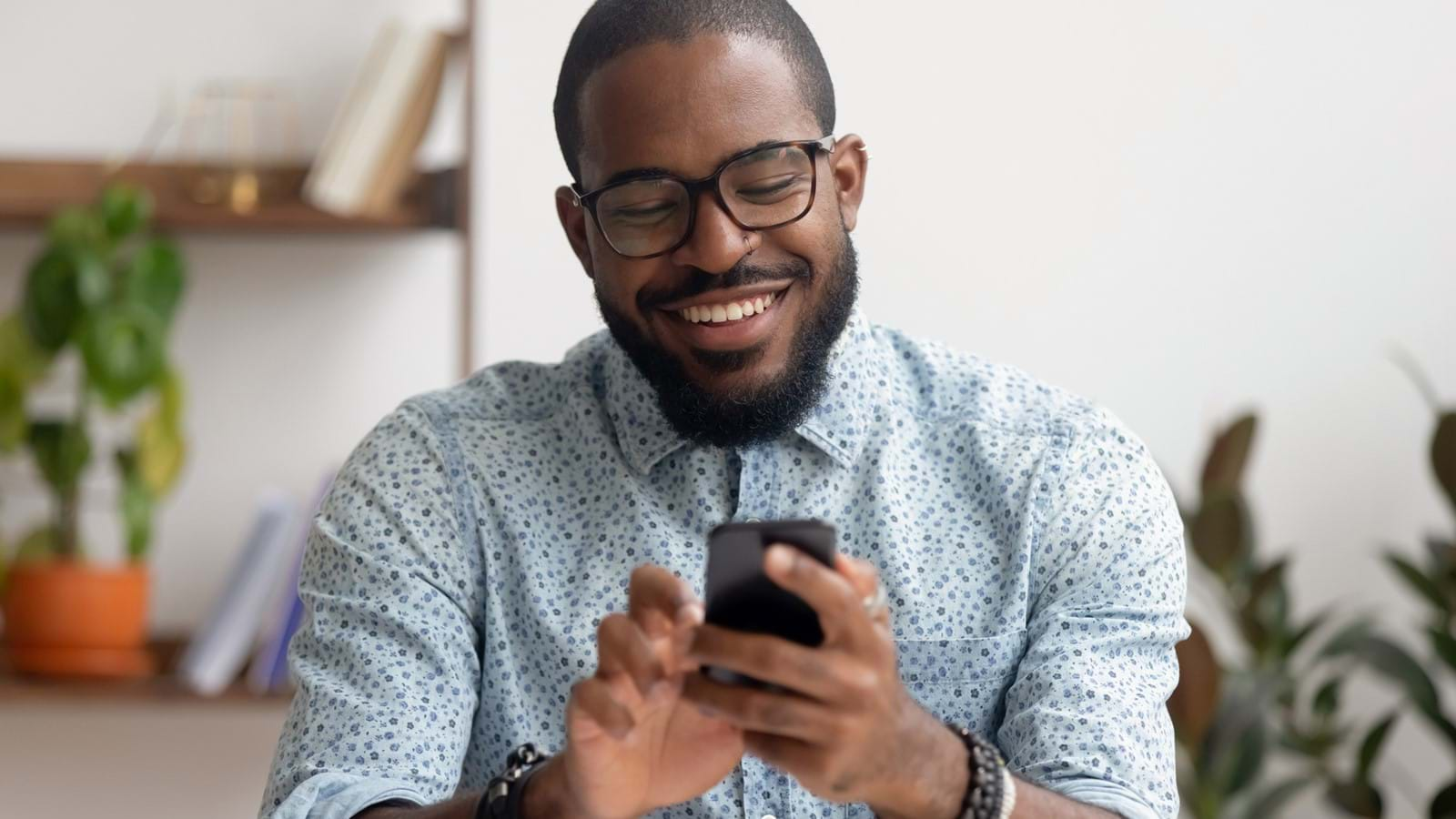 Employee using his mobile to reach his company's digital workplace, smiling and having a good experience